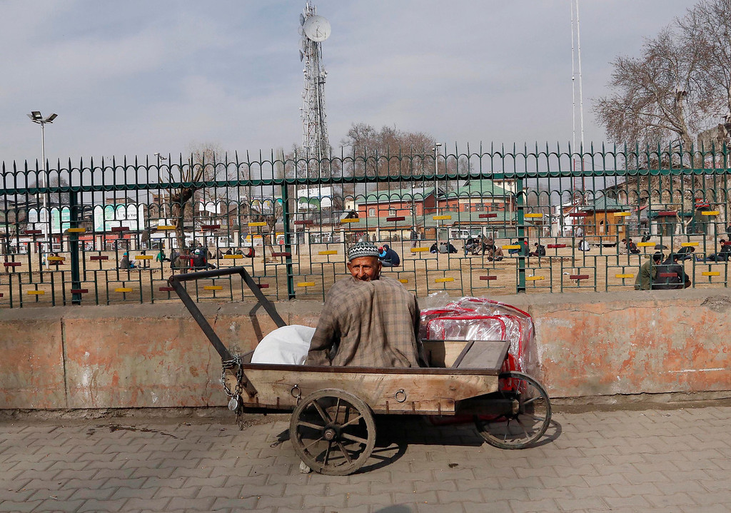 . A Kashmiri man sit on his push cart at a market on a cold day in Srinagar, India, Sunday, Dec. 29, 2013. Cold wave tightened its grip on the Kashmir valley as it continues to reel under intense cold wave for the past few days with widespread snowfall in the hilly areas. (AP Photo/Mukhtar Khan)