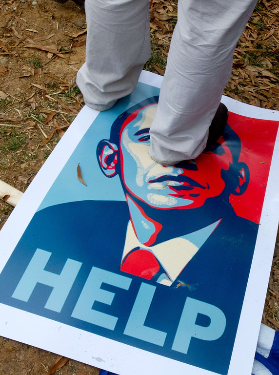 . A demonstrator stands on a poster of US President Barack Obama during a protest outside a McDonald\'s restaurant located inside of the Smithsonian Air and Space Museum as part of a nationwide protest of fast food workers December 5, 2013 in Washington, DC.  AFP PHOTO / Karen BLEIER/AFP/Getty Images