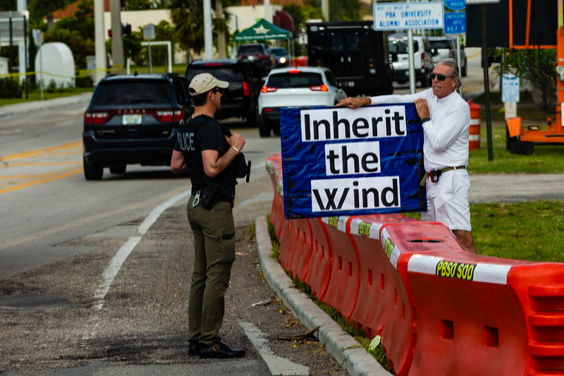 """A man stands along Southern Blvd. holding a sign reading """"Inherit the Wind"""" as President Donald J. Trump's motorcade passes by on the way toward Trump International Golf Club in West Palm Beach on Saturday, March 30, 2019. [JOSEPH FORZANO/palmbeachpost.com]"""