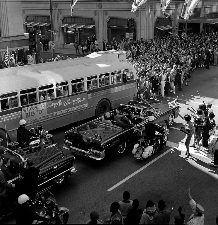 . An open limousine carrying the president and first lady approaches the intersection of Main and Ervay streets in Dallas as the presidential motorcade approaches Dealey Plaza. Texas Gov. John Connally and wife Nellie are seated in the limousine\'s jump seats. Associated Press file