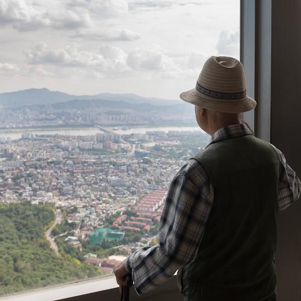 Tourist looking through window from Seoul Tower, Namsan Park, Namsan Mountain, Seoul, South Korea
