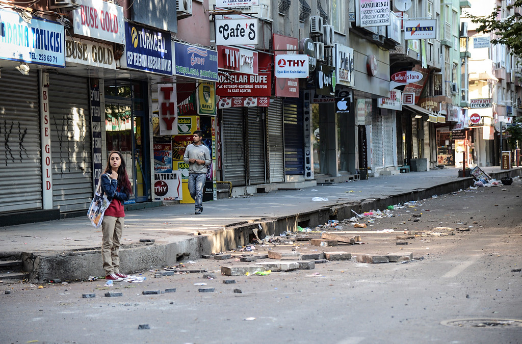 . Residents walk through a damaged street in downtown Diyarbakir on October 8, 2014, following overnight clashes with police that caused extensive damage in the city with shop fronts burned-out and buses set on fire. The Turkish army has deployed in the streets of Diyarbakir to impose a curfew, following violent protests by pro-Kurdish demonstrators in southeast Turkey angry at the government\'s lack of action against jihadists in Syria, officials said on October 8, 2014. At least 14 people were killed, 8 of the deaths came in Turkey\'s main Kurdish city of Diyarbakir where the most intense rioting took place overnight. YAS AKENGIN/AFP/Getty Images
