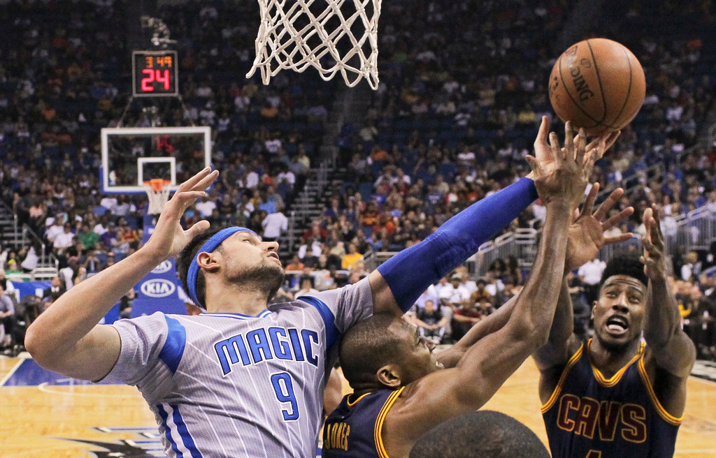 . Orlando Magic\'s Nikola Vucevic (9) battles Cleveland Cavaliers\' James Jones, center, and Iman Shumpert, right, for a rebound during the first half of an NBA basketball game, Sunday, March 15, 2015, in Orlando, Fla. (AP Photo/John Raoux)