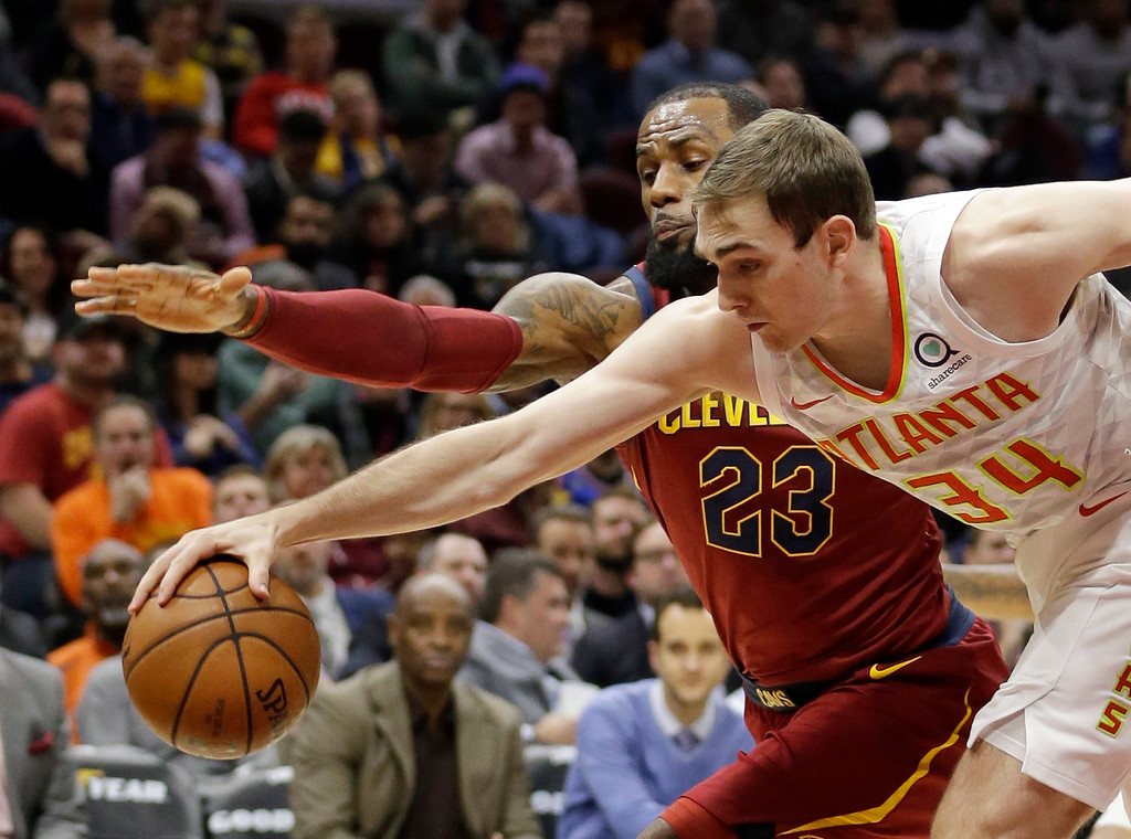 . Atlanta Hawks\' Tyler Cavanaugh (34) and Cleveland Cavaliers\' LeBron James (23) battle for a loose ball in the first half of an NBA basketball game, Tuesday, Dec. 12, 2017, in Cleveland. (AP Photo/Tony Dejak)