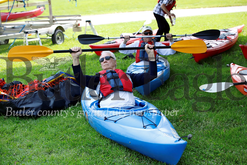Tom Rudnicki (front) and Gene Pieszak practice their paddle grip on land prior to a senior center outing at Morraine State Park. Seb Foltz/Butler Eagle