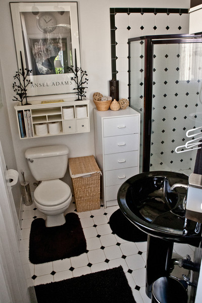 Stylishly decorated in black and white, this hip bathroom gets great natural light.