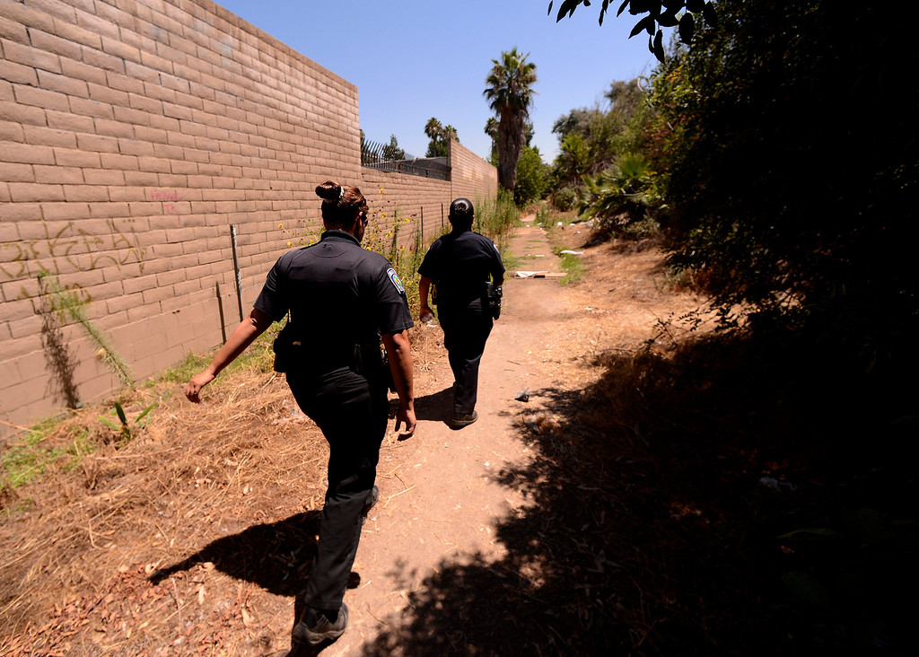 . San Bernardino Police Officers Sochilt Martinez, left, and Araceli Mata, right, look for homeless camps along the I-210 freeway in San Bernardino August 14, 2013. GABREL LUIS ACOSTA/STAFF PHOTOGRAPHER.