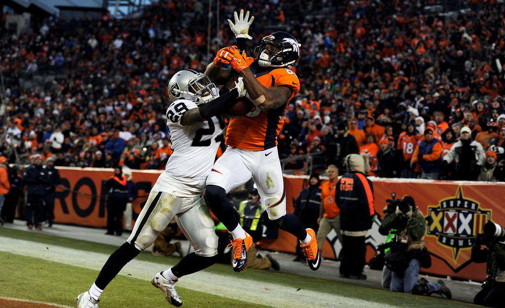 . DENVER, CO - DECEMBER 28: Demaryius Thomas (88) of the Denver Broncos misses a catch in the end zone as the play is broken up by Brandian Ross (29) of the Oakland Raiders during the third quarter.  The Denver Broncos played the Oakland Raiders at Sports Authority Field at Mile High in Denver on December, 28 2014. (Photo by Tim Rasmussen/The Denver Post)
