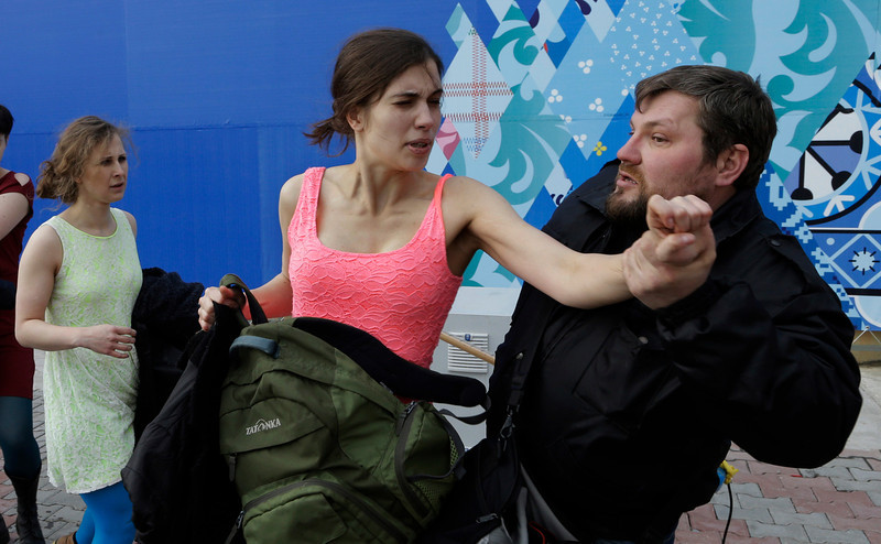. A russian security officer attacks Nadezhda Tolokonnikova and a photographer as she and fellow members of the punk group Pussy Riot, including Maria Alekhina, left, stage a protest performance in Sochi, Russia, on Wednesday, Feb. 19, 2014. The group had gathered in a downtown Sochi restaurant, about 30km (21miles) from where the Winter Olympics are being held. They ran out of the restaurant wearing brightly colored clothes and ski masks and were set upon by about a dozen Cossacks, who are used by police authorities in Russia to patrol the streets. (AP Photo/Morry Gash)