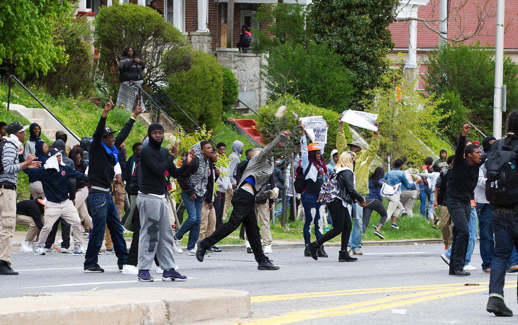 . Demonstrators throw rocks to the police, after the funeral of Freddie Gray, Monday, April 27, 2015, at New Shiloh Baptist Church in Baltimore. Gray died from spinal injuries about a week after he was arrested and transported in a Baltimore Police Department van.  (AP Photo/Jose Luis Magana)