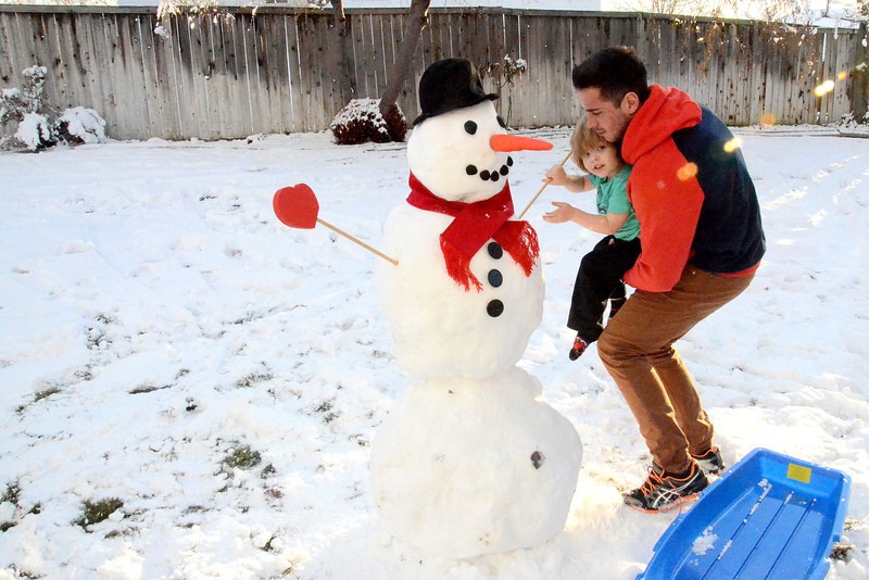 2012-12-18 –––– While at work, Sean and Olin made this cool snowman. Lisa called me so I could run home and get a picture before the sun went down. I got there just in time to see them put his arms on.