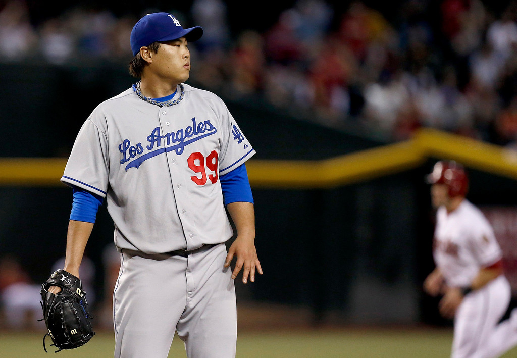 . Los Angeles Dodgers\' Hyun-Jin Ryu (99), of South Korea, looks at a Arizona Diamondbacks\' Paul Goldschmidt two-run home run as Diamondbacks\' A.J. Pollock, right, runs the bases in the first inning of a baseball game on Monday, Sept. 16, 2013, in Phoenix. (AP Photo/Ross D. Franklin)