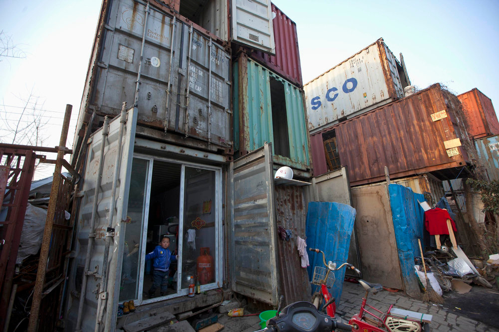 . A child stands at the door of a shipping container serving as his accommodation, in Shanghai March 4, 2013. The containers, which house different families, were set up by the landlord, who charges a rent of 500 yuan ($ 80) per month for each container. REUTERS/Aly Song