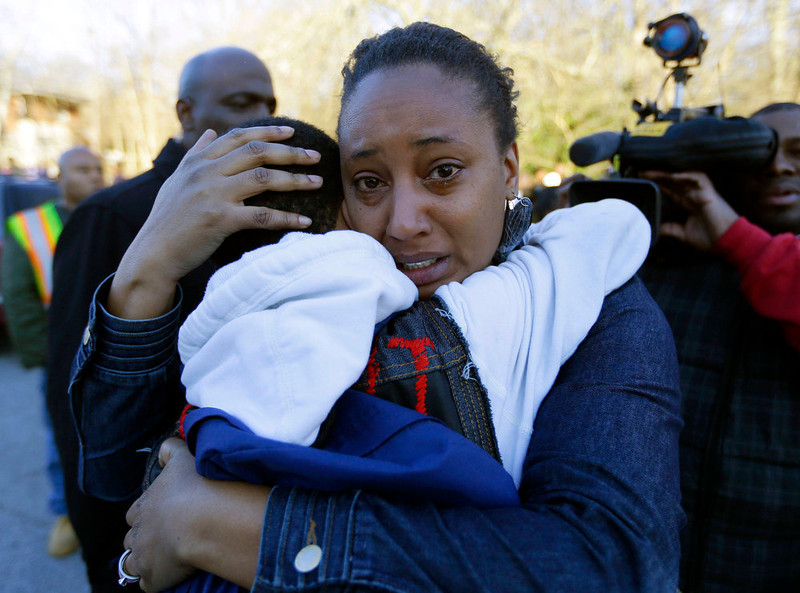 . A woman comforts a child after after a shooting at an Price Middle school in Atlanta Thursday, Jan. 31, 2013. A 14-year-old boy was wounded outside the school Thursday afternoon and a fellow student was in custody as a suspect, authorities said. No other students were hurt. (AP Photo/John Bazemore)