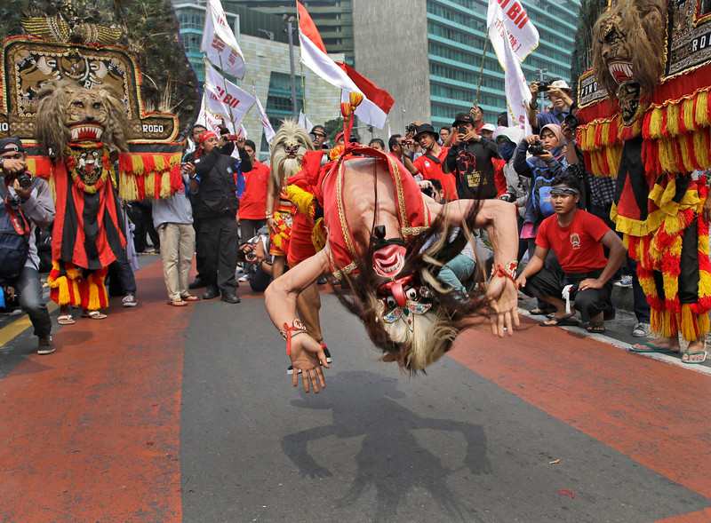 . A masked dancer somersaults as he performs during a May Day rally in Jakarta, Indonesia, Thursday, May 1, 2014. (AP Photo/Dita Alangkara)