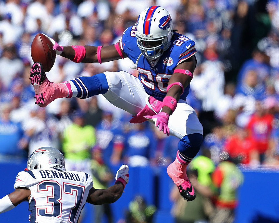 . Anthony Dixon #26 of the Buffalo Bills hurtles Alfonzo Dennard #37 of the New England Patriots  during the first half at Ralph Wilson Stadium on October 12, 2014 in Orchard Park, New York.  (Photo by Brett Carlsen/Getty Images)