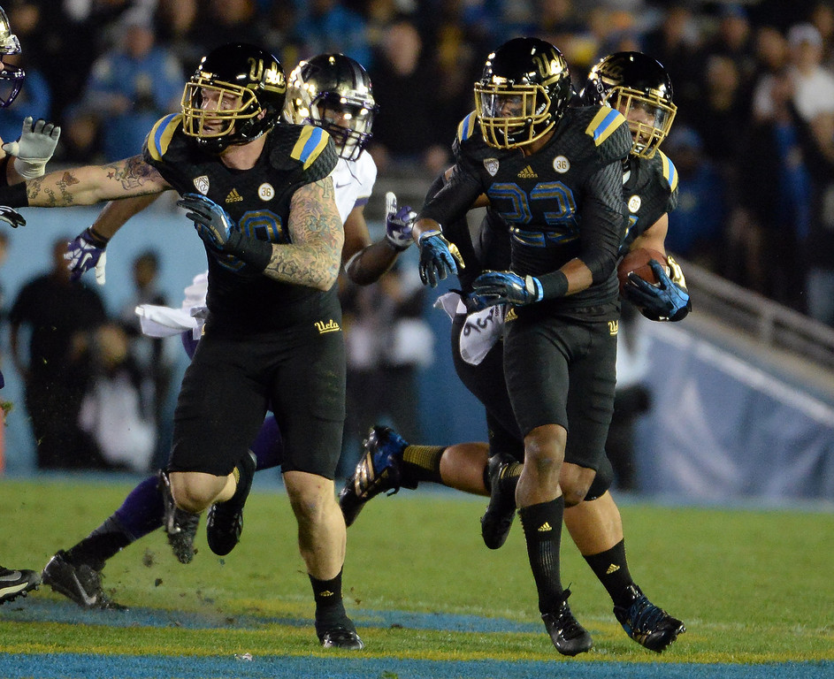. UCLA Bruins\'s Eddie Vanderdoes, right, recovers a Washington Huskies fumble during the first half of their college football game in the Rose Bowl in Pasadena, Calif., on Friday, Nov. 15, 2013.  UCLA won 41-31.   (Keith Birmingham Pasadena Star-News)