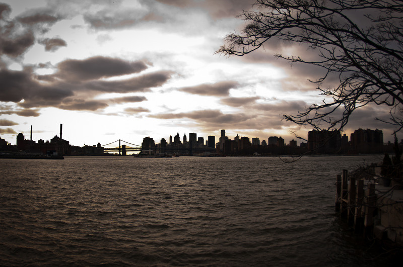 View of a city skyline including a bridge from across the water on a cloudy day by Alex Kaplan, photographer http://www.alexkaplanphoto.com