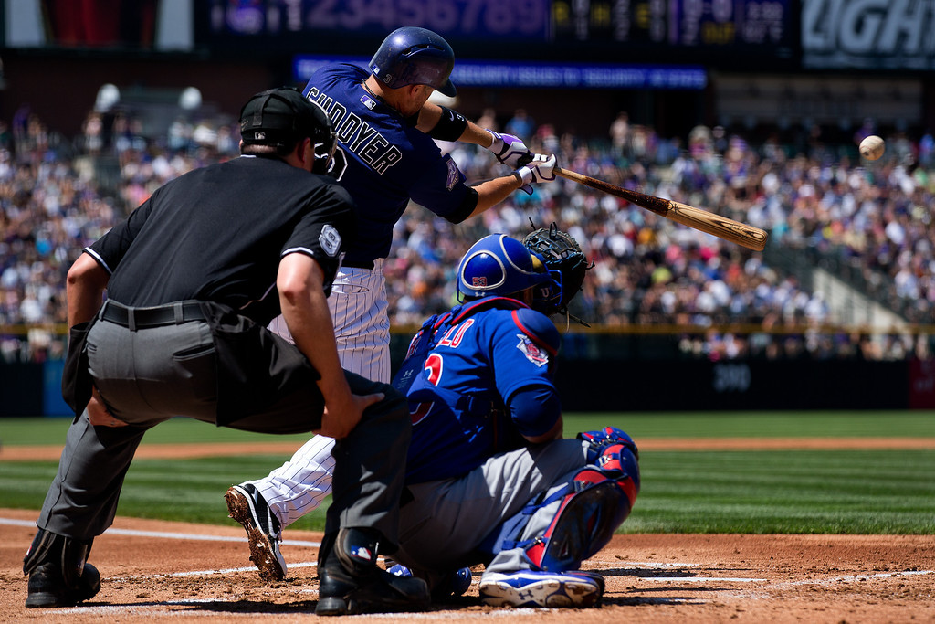 . Michael Cuddyer #3 of the Colorado Rockies hits an RBI double during the first inning as catcher Welington Castillo #53 of the Chicago Cubs and home plate umpire Lance Barrett look on at Coors Field on July 21, 2013 in Denver, Colorado. (Photo by Justin Edmonds/Getty Images)