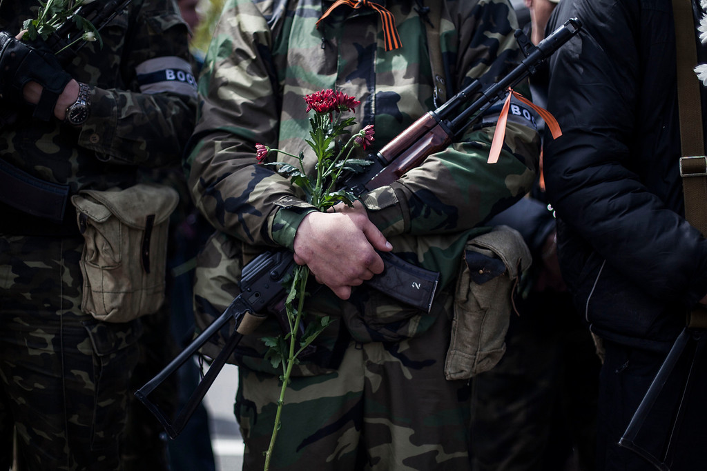 . A pro-Russian gun man holds his machine gun and a flower during the commemoration of Victory Day in Donetsk, Ukraine, Friday, May 9, 2014. Victory Day honors the armed forces and the millions who died in World War II. This year it comes as Russia is locked in the worst crisis with the West, over Ukraine, since the end of the Cold War. (AP Photo/Manu Brabo)