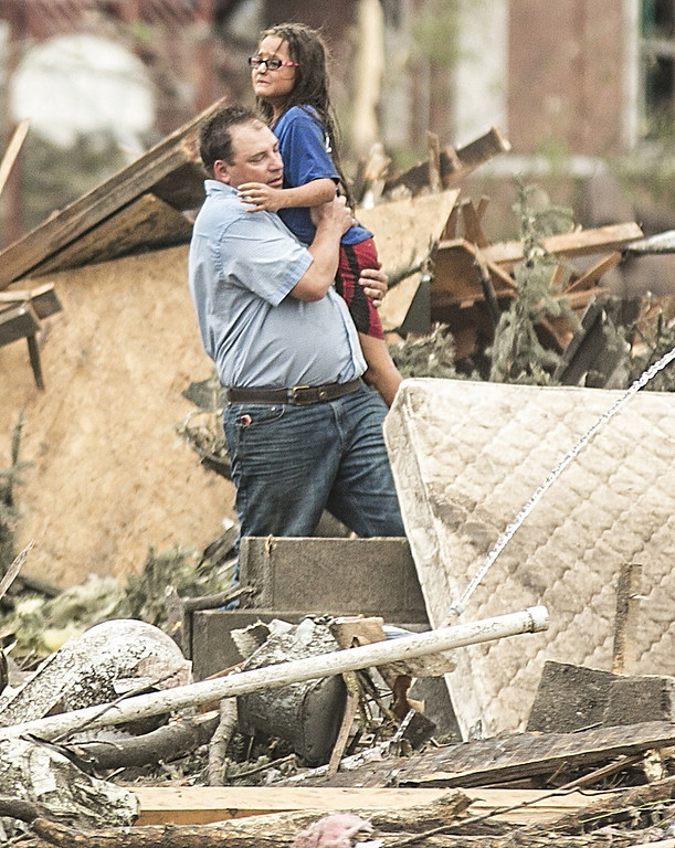 . A man holds a girl after she was pulled from the basement of her destroyed home in Pilger, Neb., Monday, June 16, 2014. A hospital spokeswoman says at least one person is dead and at least 16 more are in critical condition after two massive tornadoes swept through northeast Nebraska. (AP Photo/Mark \'Storm\' Farnik)