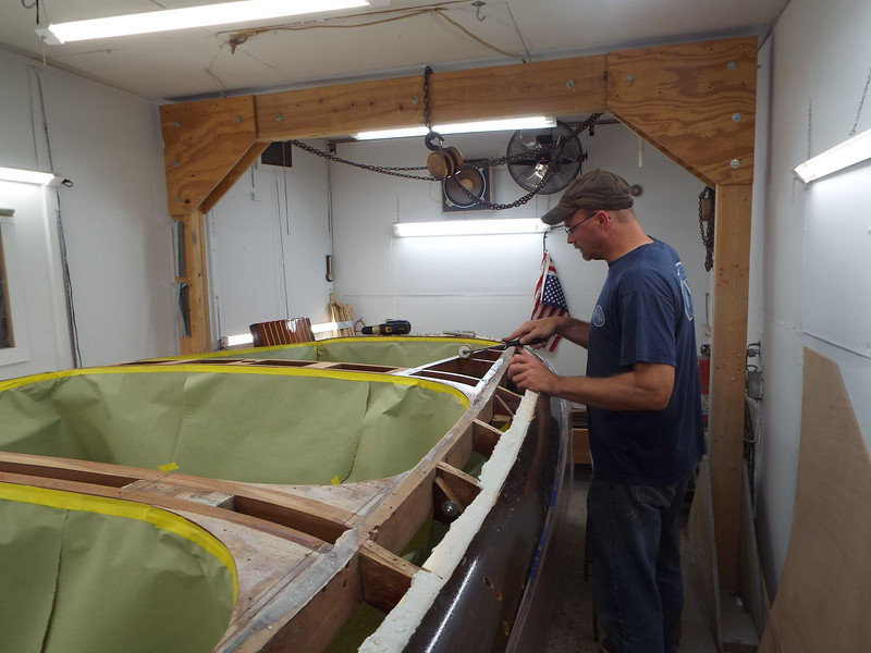 Applying epoxy to the hull so the plywood skin can be applied.