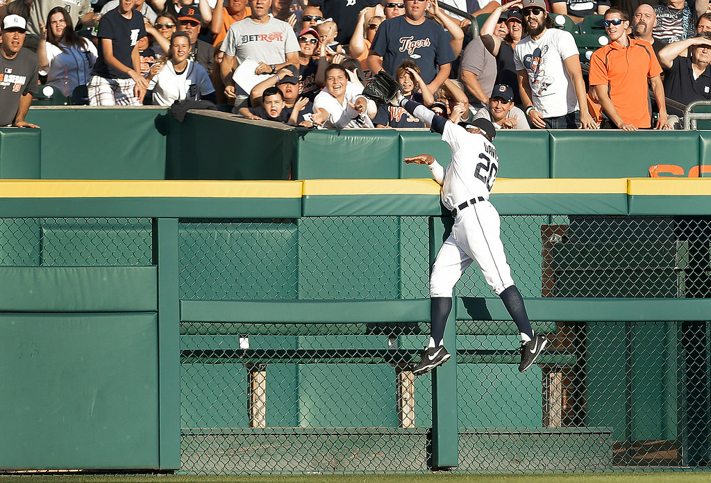 . Detroit Tigers left fielder Rajai Davis tries but can\'t reach a Los Angeles Dodgers\' Juan Uribe two-run home run in the first inning of a baseball game in Detroit, Tuesday, July 8, 2014. (AP Photo/Paul Sancya)