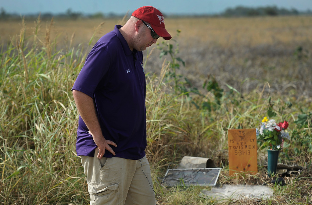 . OKLAHOMA CITY, OK - Aug. 6: Erik Fox, fellow storm chaser and friend of the TWISTEX team, stands near a small memorial site that appeared on the edge of Reuter Road, just east of Radio Road, where the TWISTEX team\'s white Chevrolet Cobalt was found in a farmer\'s field. Fox and several volunteers combed the fields for nearly a half-mile stretch just after the tornado, searching for belongings of the three victims. The TWISTEX storm chasing crew, including Tim Samaras, his son Paul Samaras, and Carl Young, were killed in the El Reno tornado near Oklahoma City on May 31, 2013.(Photo By Kathryn Scott Osler/The Denver Post)