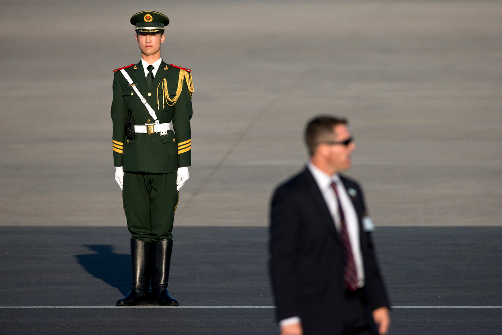 . A Chinese paramilitary policeman, back, a U.S. secret service officer, front, as they guard a tarmac before the landing of a plane carrying U.S. First Lady Michelle Obama, her daughters and her mother, arrive at Capital International Airport in Beijing, China, Thursday, March 20, 2014. Michelle Obama has arrived in Beijing with her mother and daughters to kick off a seven-day, three-city tour where she will focus on education and cultural exchange. (AP Photo/Alexander F. Yuan, Pool)