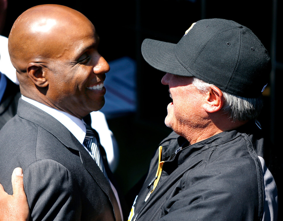 . Former Pittsburgh Pirates outfielder Barry Bonds, left is greeted by current manager Clint Hurdle during opening day ceremonies before the baseball game between the Pittsburgh Pirates and the Chicago Cubs on Monday, March 31, 2014, in Pittsburgh.  (AP Photo/Keith Srakocic)