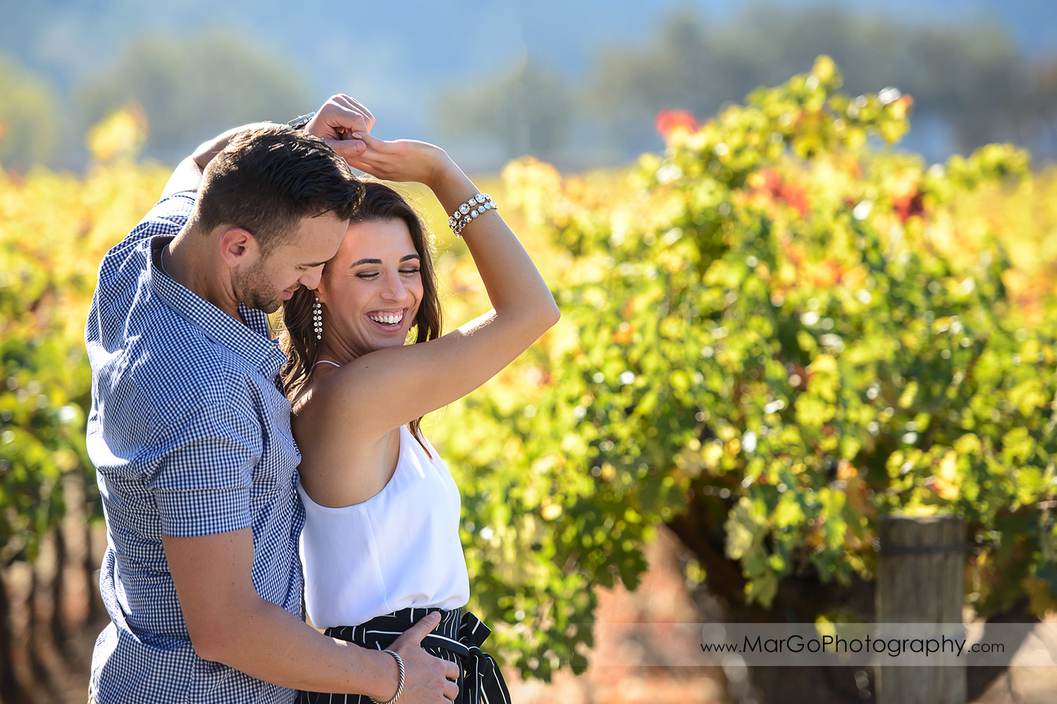 man in blue shirt and woman in white top dancing in front of vineyard during Napa Valley engagement session at Grgich Hills Estate in Rutherford