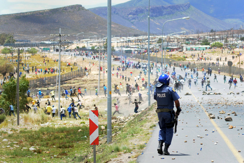 Description of . Members of the South African Police Services clash with striking farmworkers during violent clashes, on January 10, 2012 in de Doorns, a small farming town about 140Km North of Cape Town, South Africa. The farm workers have said that they they will not return to work on the fruit growing region's farms until they receive a daily wage of at least R150($17) per day, which is about double what they currently earn.  AFP PHOTO / RODGER BOSCH/AFP/Getty Images