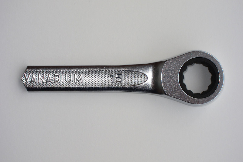 A 15 mm ratcheting box end wrench was modified by cutting and filing it to fit the angles within the socket.  This wrench was chosen because it had 0 degrees offset and as an added bonus, it was ratcheting.
