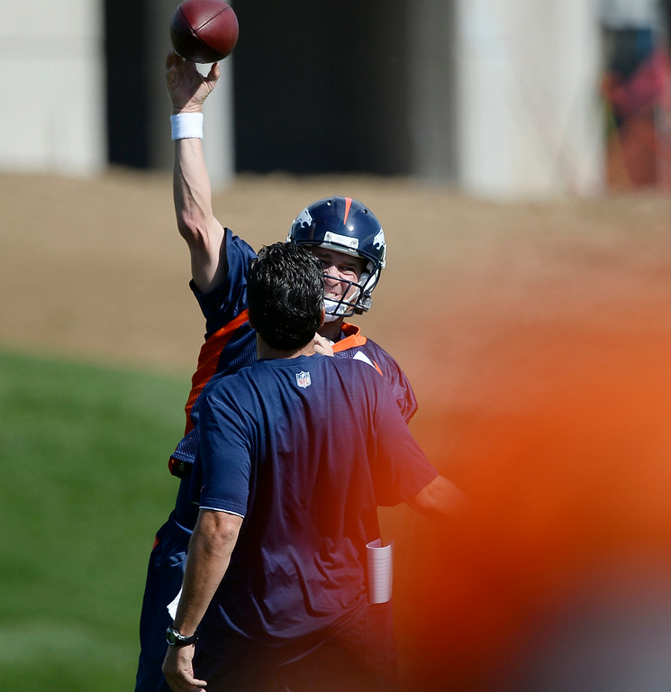 . Denver Broncos quarterback Peyton Manning (18) throws a pass over quarterbacks coach Greg Knapp during the first day of the Denver Broncos 2014 training camp July 24, 2014 at Dove Valley. (Photo by John Leyba/The Denver Post)