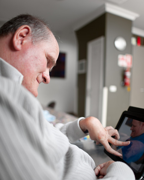 Man with a disability looks at photos on computer in his living room