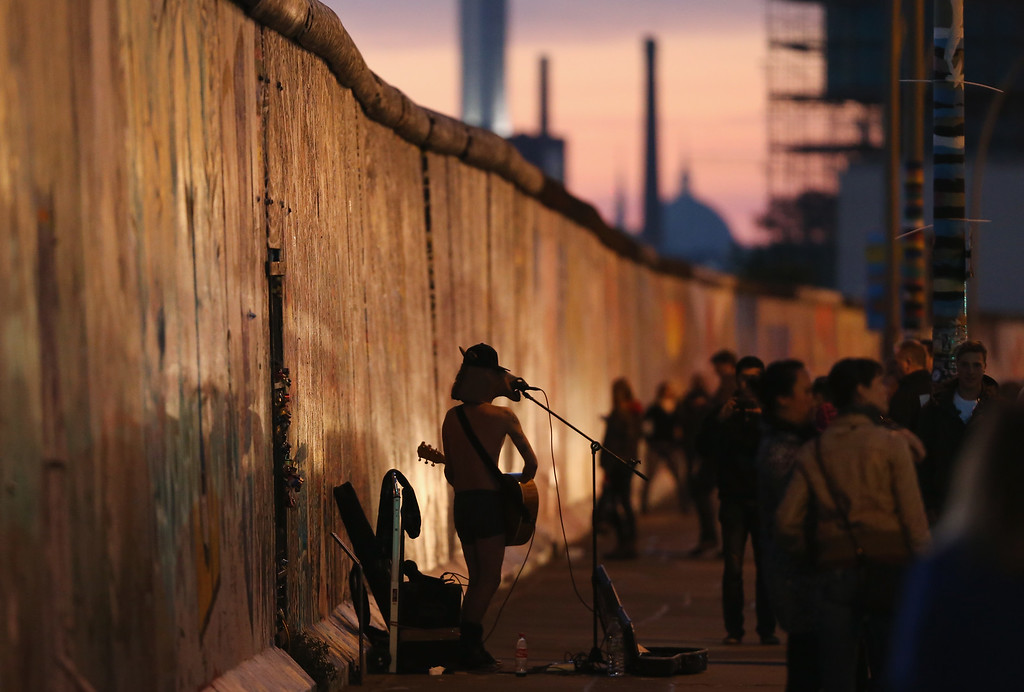 . A street musician wearing a mask performs at the East Side Gallery, which is a 1.3 km-long original section of the Berlin Wall and is today a popular tourist attraction, on October 28, 2014 in Berlin, Germany.  (Photo by Sean Gallup/Getty Images)