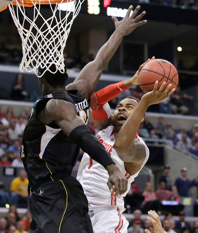 . Wichita State center Ehimen Orukpe, left, defends as Ohio State forward Deshaun Thomas takes aim during the first half of a West Regional final in the NCAA men\'s college basketball tournament, Saturday, March 30, 2013, in Los Angeles. (AP Photo/Jae C. Hong)