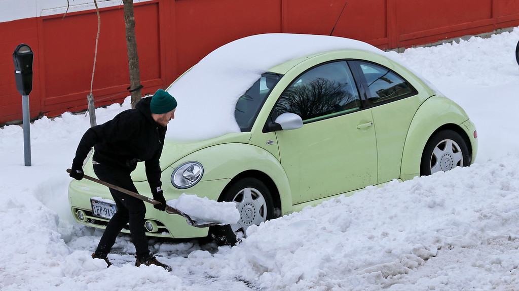 . Ross Munroe digs out his car in Richmond, Va., Monday, Jan. 25, 2016.  The storm dropped snow from the Gulf Coast to New England, with near-record snowfalls tallied from Washington, D.C. to New York City.  (AP Photo/Steve Helber)