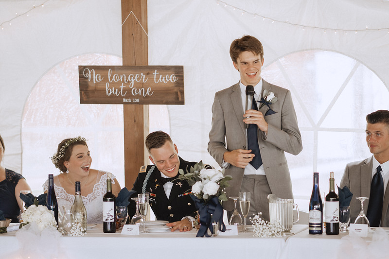 The bride and groom laugh as the groom's brother delivers a funny speech.