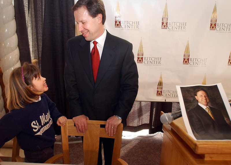 . Head coach for the University of Denver Pioneers hockey team, George Gwozdecky talks with his daughter, Adrienne, 8, after she put a picture of him up on a podium after a press conference announcing his contract extension with the Pioneers. Andy Cross/The Denver Post