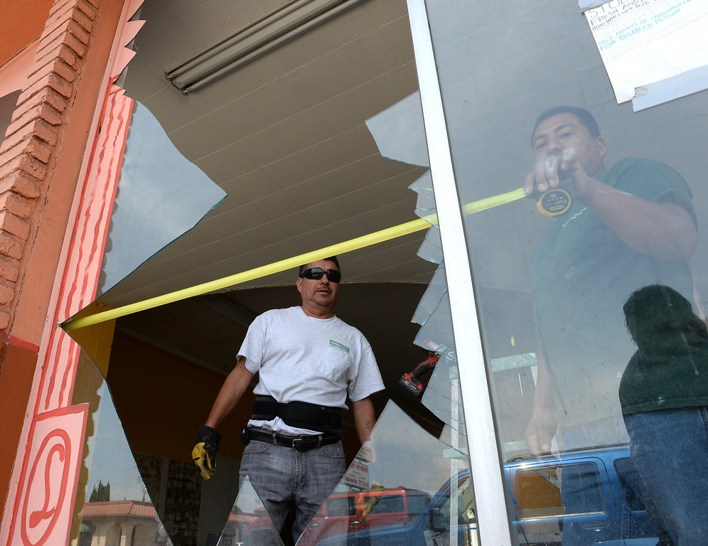 . Martin Jimenez, left, and Daniel Bonilla measure a broken front window of a former tile store after the 5.1 earthquake centered in La Habra on Saturday March 29, 2014. (Staff Photo by Keith Durflinger/Whittier Daily News)