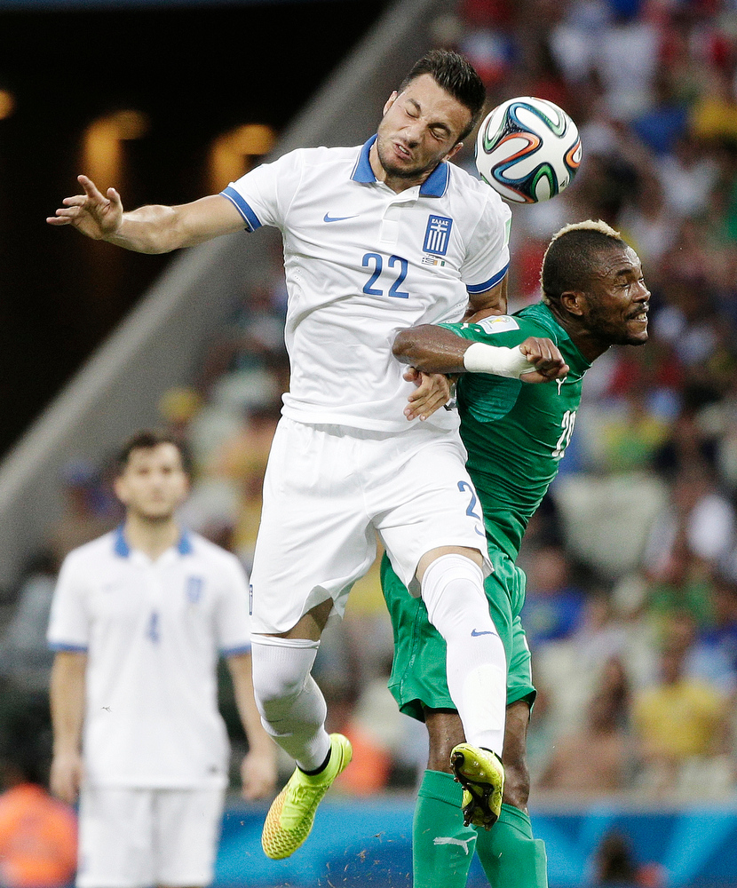 . Greece\'s Andreas Samaris goes up against Ivory Coast\'s Serey Die to head the ball during the group C World Cup soccer match between Greece and Ivory Coast at the Arena Castelao in Fortaleza, Brazil, Tuesday, June 24, 2014. (AP Photo/Christophe Ena)