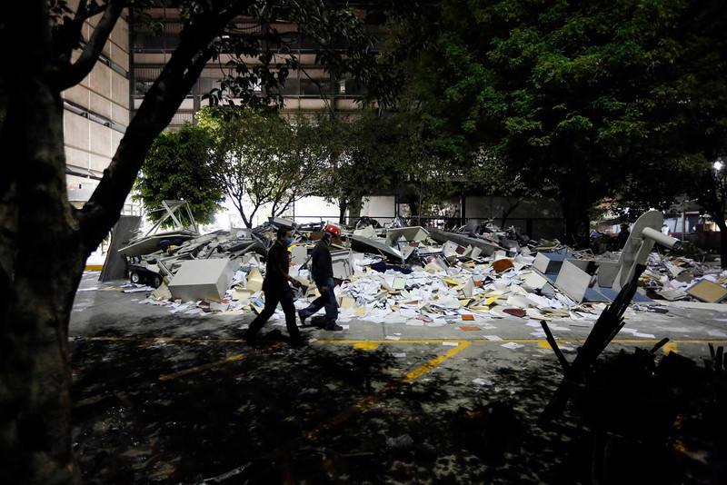 . Rescue workers walk past debris piled outside the headquarters of state-owned oil giant Pemex in Mexico City January 31, 2013. A powerful explosion rocked the Mexico City headquarters of Pemex on Thursday, killing at least 25 people, injuring more than 100 and trapping others inside. Picture taken January 31, 2013.  REUTERS/Bernardo Montoya