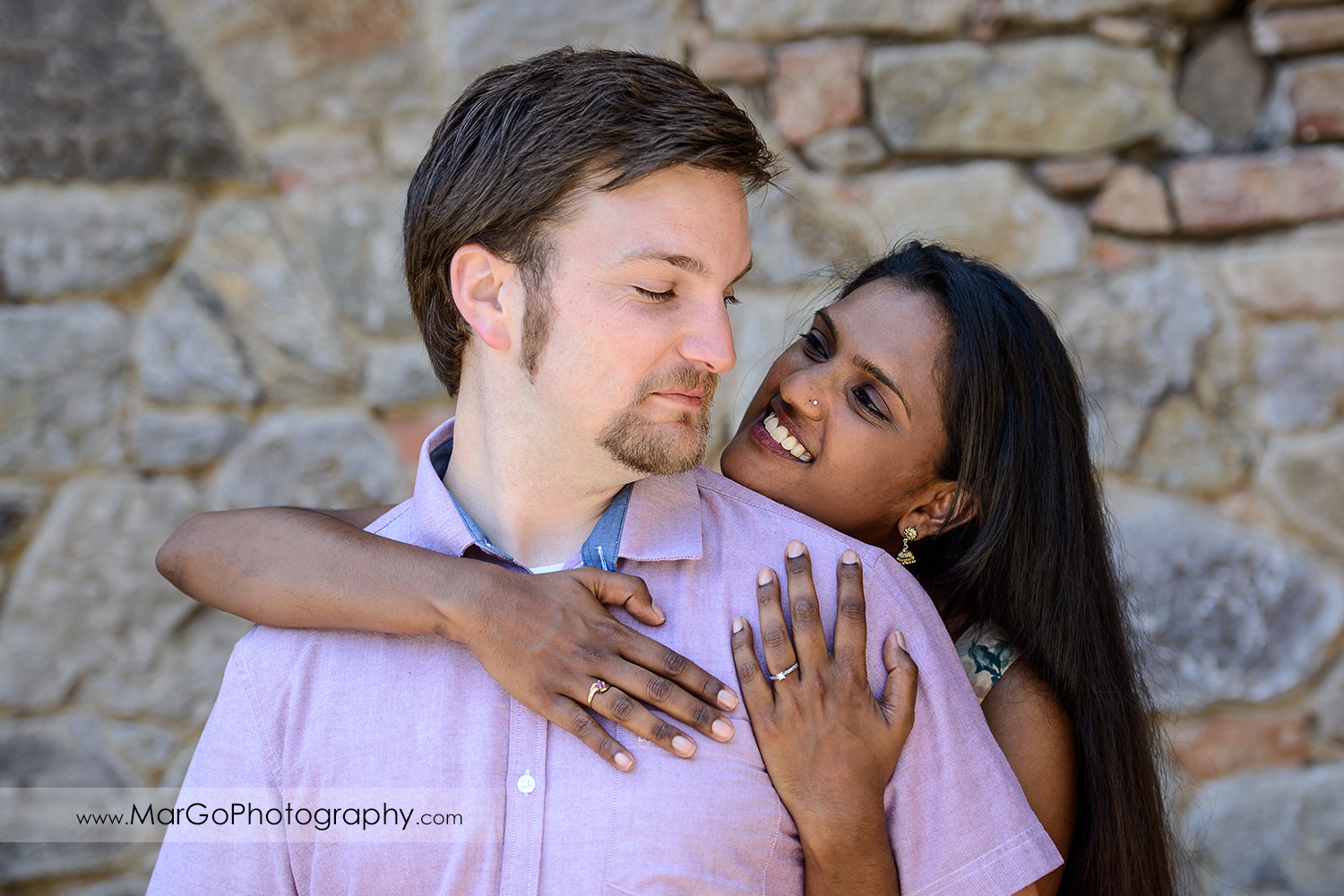 Indian woman in flower dress holding man in pink shirt during engagement session at Castello di Amorosa in Calistoga