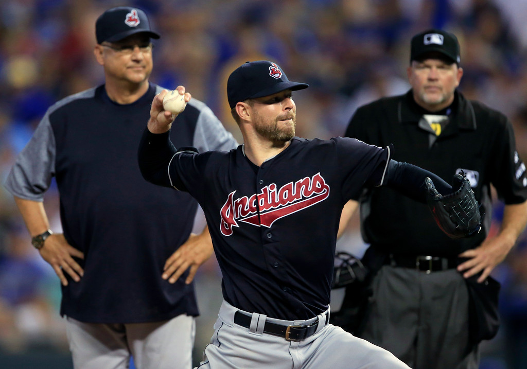 . Cleveland Indians starting pitcher Corey Kluber, front, takes a practice pitch in front of manager Terry Francona, left, and umpire Ron Kulpa during the sixth inning of a baseball game against the Kansas City Royals at Kauffman Stadium in Kansas City, Mo., Friday, Aug. 18, 2017. Kluber turned his ankle on the previous play. (AP Photo/Orlin Wagner)