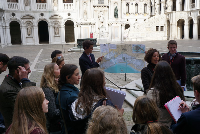 Betta Morelli giving a tour in Palazzo Ducale with Matthew and Henry holding the map for her