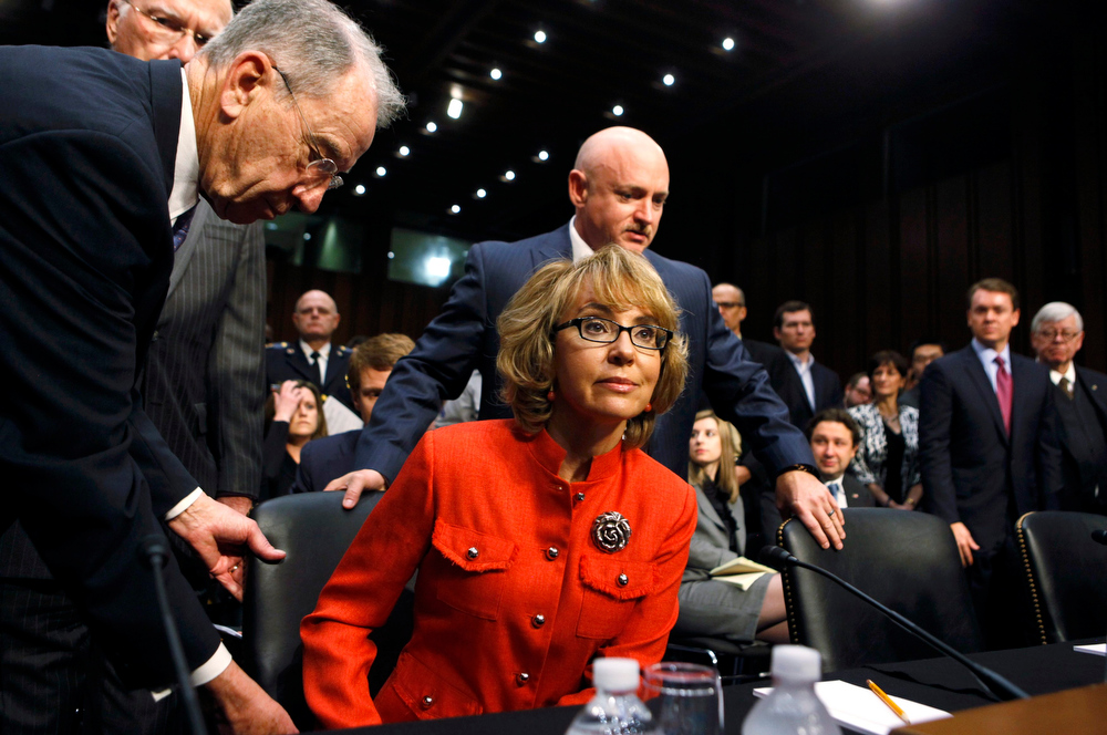 Description of . Former U.S. Rep. Gabrielle Giffords arrives with her husband, retired U.S Navy Captain Mark Kelly (R), prior to a Senate Judiciary Committee hearing on gun violence, on Capitol Hill in Washington January 30, 2013. The hearing comes six weeks after the massacre of 26 people at a Connecticut school ignited new calls to fight gun-related violence. Committee Chairman Patrick Leahy (D-VT) and Charles Grassley (R-IA) look on at left. REUTERS/Larry Downing
