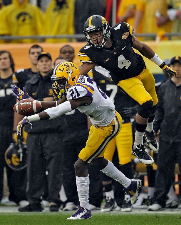 . LSU defensive back Rashard Robinson (21) knocks a pass away from Iowa wide receiver Tevaun Smith (4) during the first quarter of the Outback Bowl NCAA college football game Wednesday, Jan. 1, 2014, in Tampa, Fla. (AP Photo/Chris O\'Meara)