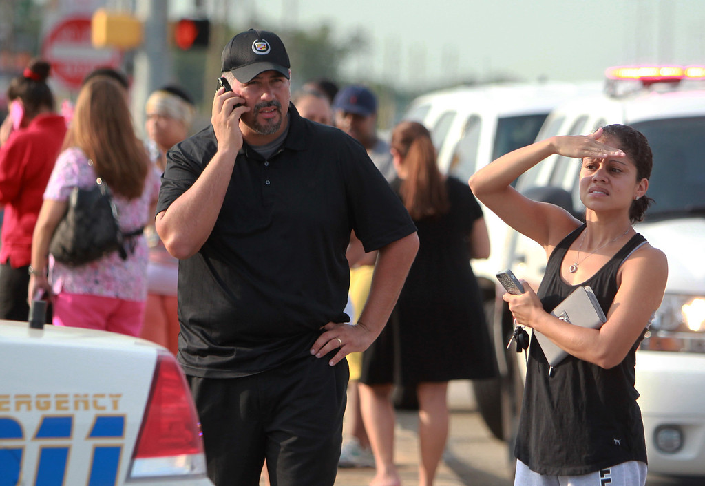 . Adults wait outside Spring High School after at least one person was killed and others injured during an altercation inside the school Wednesday, Sept. 4, 2013, in Spring, Texas.  (AP Photo/The Houston Chronicle, Mayra Beltran )