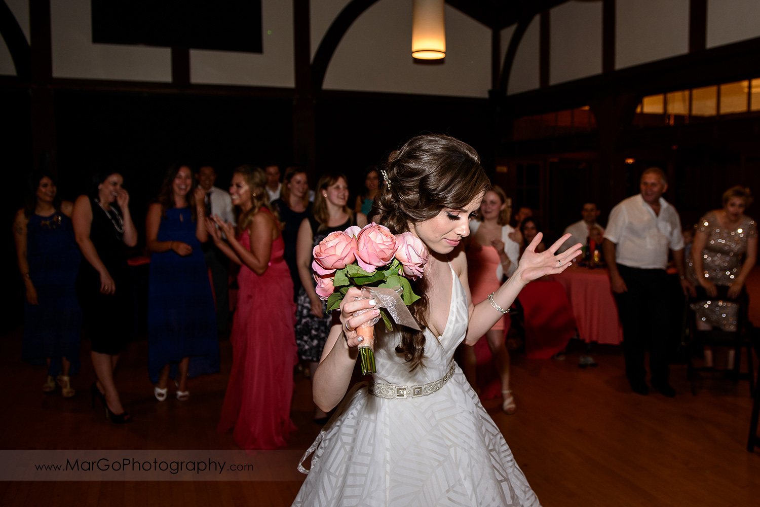 bride atossing bouquet during wedding reception at Saratoga Foothill Club